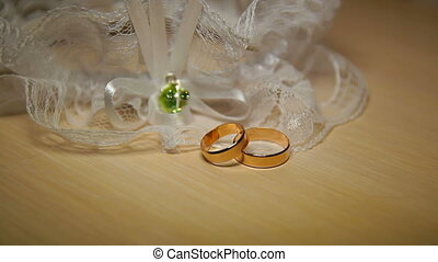 Wedding Rings With Lace On The Table - Two wedding rings are...