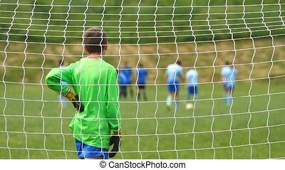 Children soccer goalkeeper from behind goal net