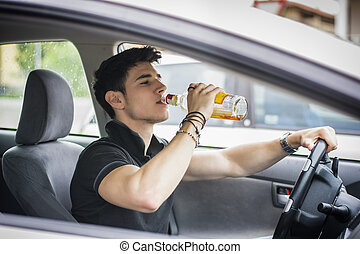 Young man driving his car while drinking alcohol - Young...