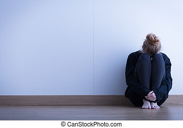 Girl sitting curled up on the floor