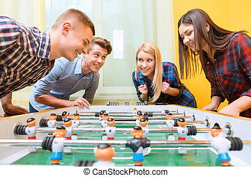 Happy friends playing table hockey - Boys vs girls. Young...