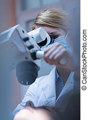 Directing the magnifying glass - Young dentist directing...