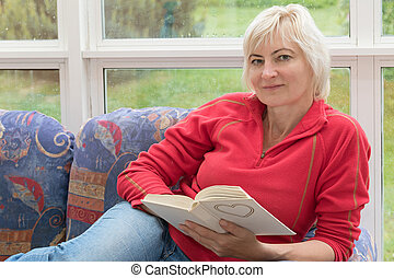 Blonde middle-aged woman is relaxing with a book in her hands