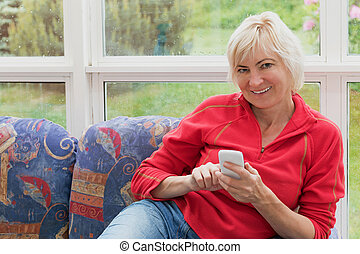 Blonde middle-aged woman is holding a cell phone