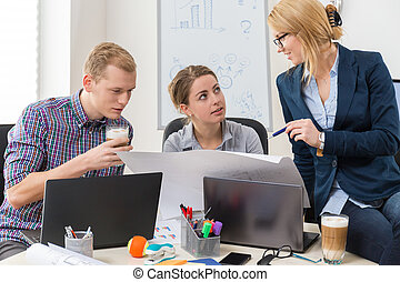 Office workers talking about guidelines to project