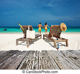 Couple in yellow relax on a beach at Maldives - Couple in...