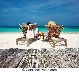 Couple in white relax on a beach at Maldives - Couple in...