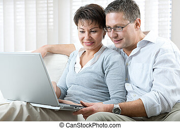 couple with laptop - happy couple using laptop at home