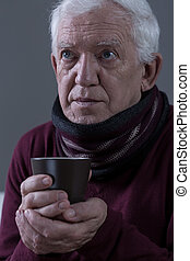 Senior with flu holding cup of warm tea