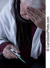 Pensioner with fever - Sick pensioner measure his...