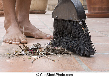 Barefoot closeup sweeping outdoor patio floor - Closeup pile...