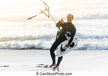 Kitesurfer smiling and waving to the camera on a beautiful...