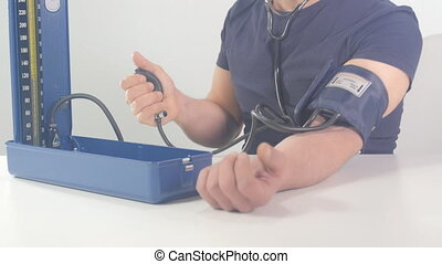 blood pressure self checking - man measuring his blood...