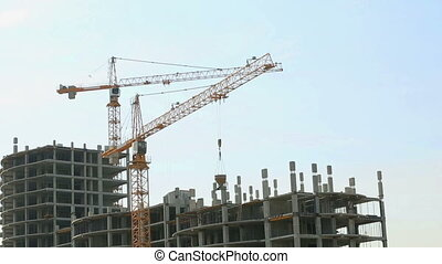 View of cranes working on building site. Sky background