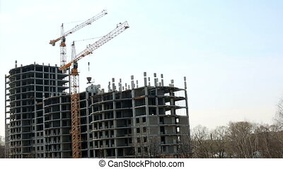 Construction of apartment building. Cranes working