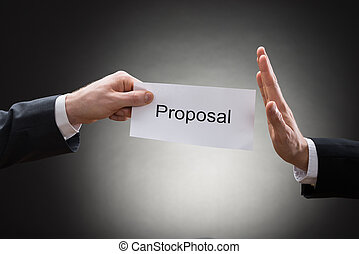 Close-up Of Man's Hand Refusing Proposal Sign On Paper