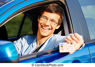 Guy shows driving license from car - Happy young man in...
