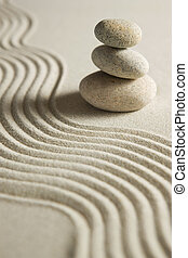 Balance - Stack of stones on raked sand Zen concept