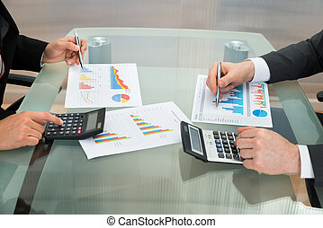 Businessmen Analyzing The Graph On Office Desk - Close-up Of...