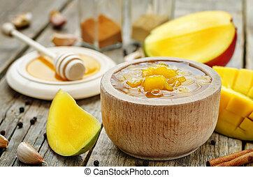 mango chutney on a dark wood background. the toning....