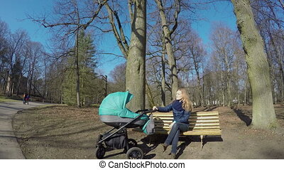 mother bench stroller - Happy young mother with baby in...