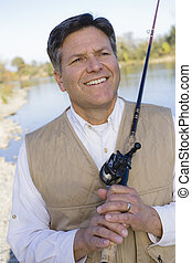 Man With Fishing Pole - Man Standing By A River With A...