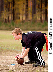 Hike - A young boy hiking a football during a game