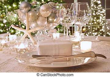 Elegantly lit holiday dinner table with white ribboned gift...