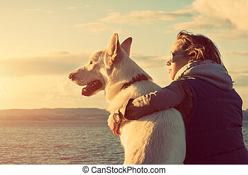 Young attractive girl with her pet dog at a beach, colorised...