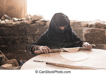 Old Arab woman prepares bread in a Bedouin village