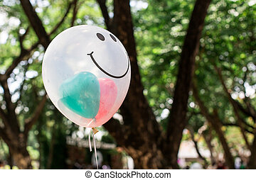 transparent balloon with smile face on green bokeh...