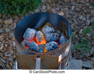 Flaming hot charcoal briquettes in a grill starter