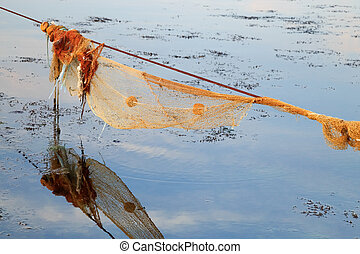 Empty fishnet for mussel in the sea at sunset.