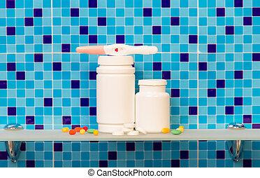 Pregnancy test with pills on bath shelf on blue background