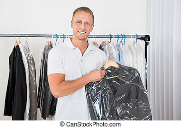 Man Holding Coat In Dry Cleaning Store - Young Happy Man...