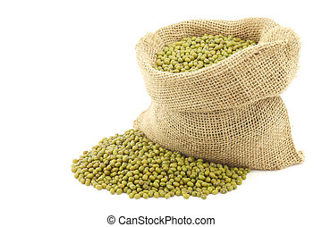 Mungo beans (Vigna radiata) in a burlap bag on a white...