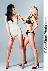 Studio fashion shot: opposition of two lovely girls blonde...