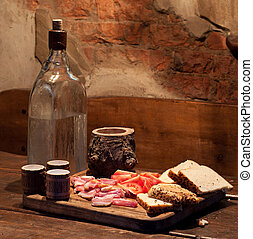 Ukrainian Moonshine and bacon, tomato and bread on table