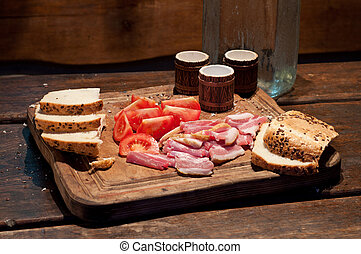 Bacon, tomato, bread and vodka on the table