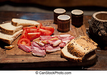 Bacon, tomato, bread and moonshine on the table