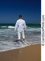 Barefoot guy standing near the sea, vertical