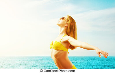 young happy woman on the beach in a bikini