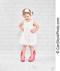 little girl fashionista in big pink heeled shoes - little...