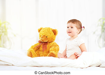 cute little child girl hugging teddy bear in bed - the cute...