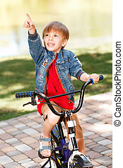 Little smiling boy riding bicycle and pointing upwards -...