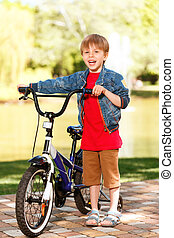 Small smiling boy standing next to bike - Feeling happiness...