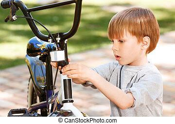 Close up of little boy repairing his bike - In repairing...
