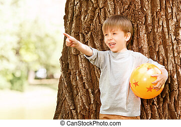Boy under tree with rubber ball pointing upwards - What is...