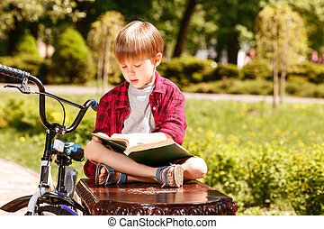 Boy sitting on bench and reading book.
