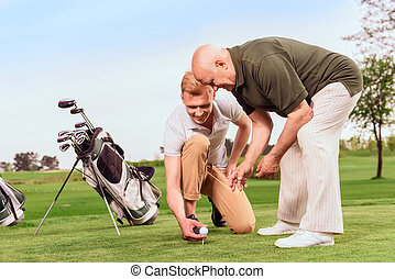 Two men putting ball on tee at course - Preparatory work....